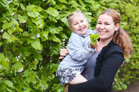 Happy mom and little daughter smiling  Small child on woman hands   Copyspace  Green leaf as background photo