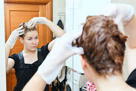 hair coloring: Portrait of pretty Caucasian beautiful woman dyeing hairs at domestic bathroom