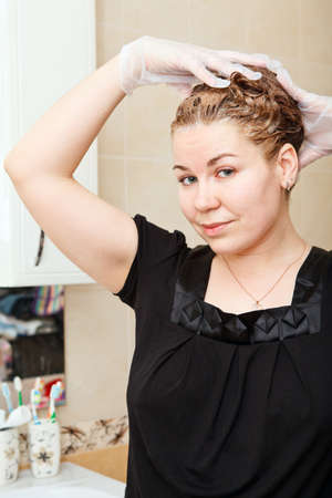 Portrait of pretty Caucasian beautiful woman dyeing hairs at domestic bathroom Stock Photo - 14127102