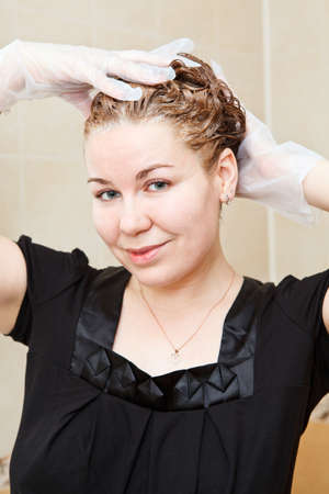 Portrait of pretty Caucasian beautiful woman dyeing hairs at domestic bathroom photo