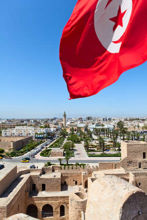 Aerial view of streets at Monastir city, Tunisia  Minaret of mosque and Ribat as a fortress  Red Tunisian flag  Horizontal photo