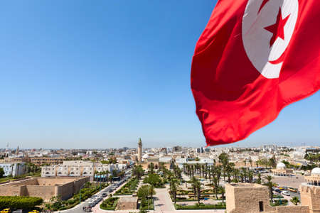 Top view of streets at Monastir city, Tunisia  Minaret of mosque and Ribat as a fortress  Red Tunisian flag