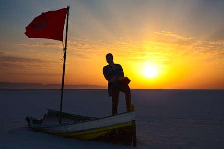 salina: Woman silhouette with flag of Tunisia against sunrise lights  Broken boat on salina area