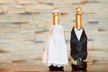 Two bottles of champagne in bride and groom clothes in table  Copy space photo