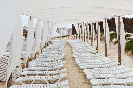 White plastic sunbeds in sandy beach under big parasol photo