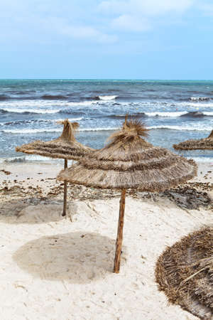 Mediterranean stormy sea and sandy beach with parasols photo
