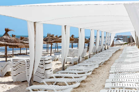 White plastic sunbeds in sandy beach under big parasol photo