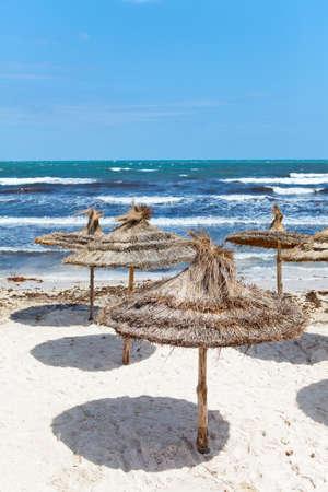 Mediterranean stormy seacoast and palm leaf parasols photo