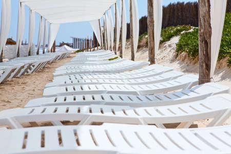Empty white plastic deck chairs on sandy beach under big parasol photo