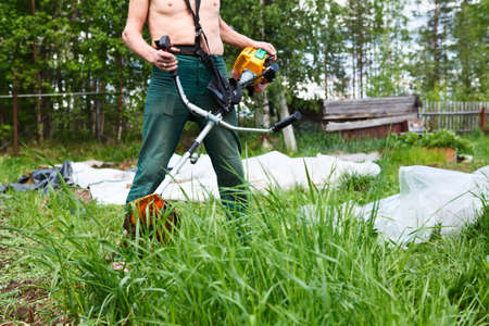 Unrecognizable person a lawn-mower with chopper trimer mowing grass  Focus on trimer photo
