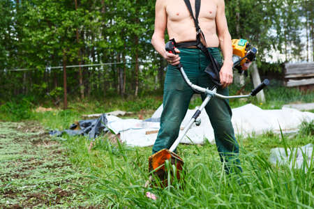 Unrecognizable man a lawn-mower with chopper trimer mowing grass  Focus on trimer photo
