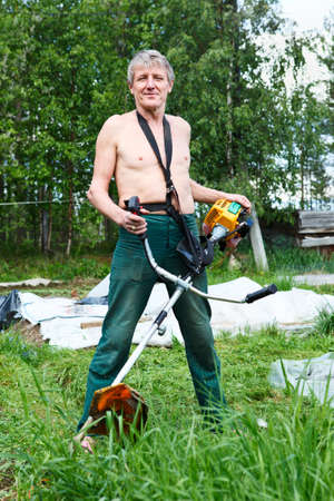 Mature Caucasian man a lawn-mower with chopper trimer mowing grass  photo