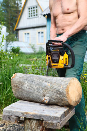 Caucasian senior male trying to start chainsaw for cutting the log photo