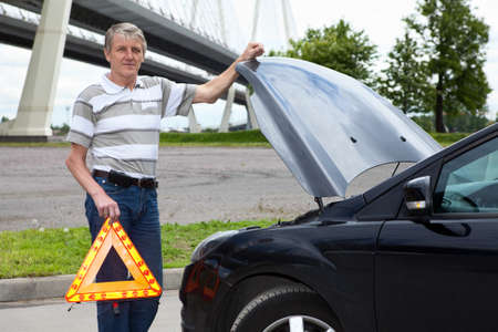 open autocar auto: Mature man holding emergency triangle and opened car hood