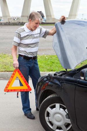 Mature man with emergency triangle standing in front of land vehicle Stock Photo - 14130971