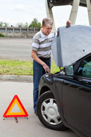 Mature man with opened car hood and emergency triangle sign on road photo