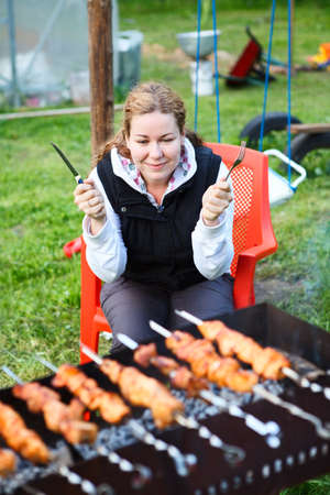 Woman with fork and knife in hands sitting and waiting for grill meat photo