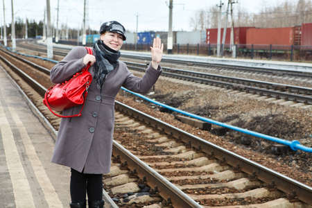 Portrait of happy fashion young Caucasian woman standing on railway station  Looking far away  Copy space photo