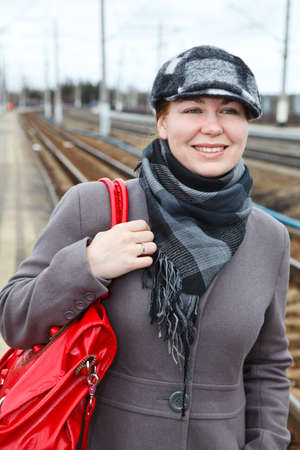 Portrait of fashion young woman in coat and cap with red bag photo