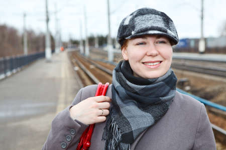 Portrait of happy smiling woman in cap standing on railway station photo