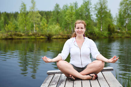 Happy woman in lotos pose sitting on wooden boards on lake edge  Copyspace photo