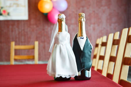 Two bottles of champagne in bride and groom clothes on table. photo