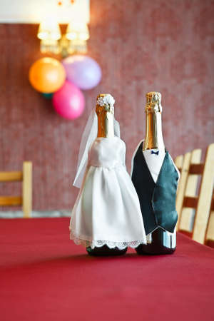 Two bottles of champagne wearing like a bride and groom standing on table. photo