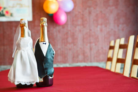 Two bottles of champagne wearing like a bride and groom on table. Copy space photo