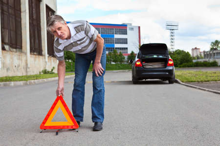 wayside: Mature man sets triangle warning sign on road  Car with blinker lights on wayside Stock Photo