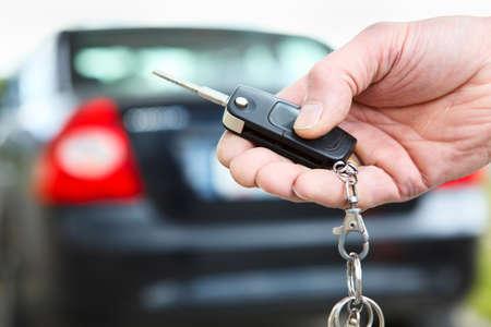 thumb keys: La llave de encendido con control remoto de sistemas de alarma de coche en la mano, de cerca Foto de archivo