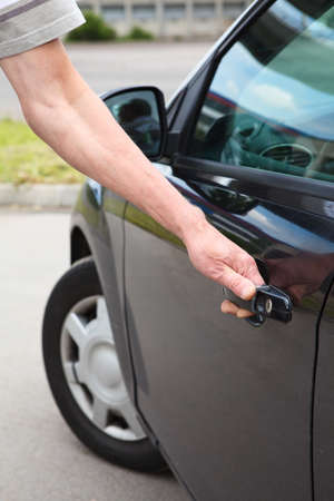 open car door: Close up of Caucasian man opening door of black car