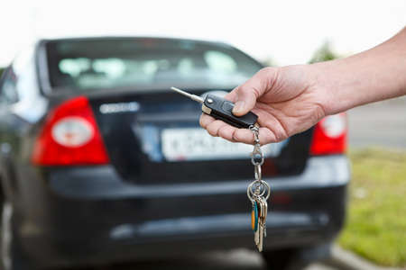 Ignition key with remote control of car alarm systems in male hand with defocused car, close up Stock Photo - 14338011