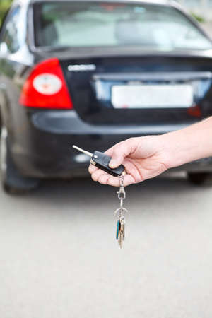car rental: Man s hand presses on the remote control of car alarm systems, close up