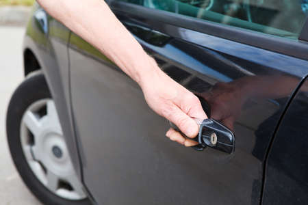 open car door: Male a driver opening car door of black land vehicle Stock Photo