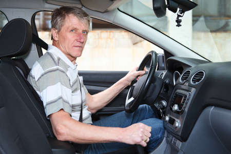 Experienced driver mature Caucasian man sitting inside of own car photo