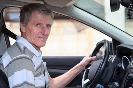 one senior man only: Experienced driver mature Caucasian male holds steering wheel in own car Stock Photo