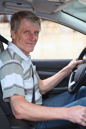 Mature experienced driver a Caucasian male sitting inside of his car photo