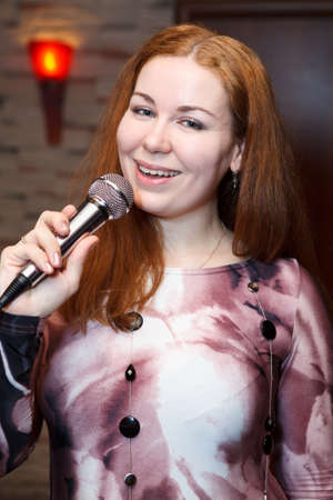 Attractive woman singing a song with microphone photo
