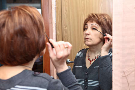 Mature Caucasian woman applying make up against mirror in domestic room photo