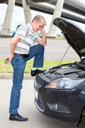 Confused driver standing front of car with opened engine compartment hood photo