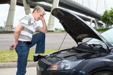 Confused mature driver standing front of car with opened engine compartment hood photo