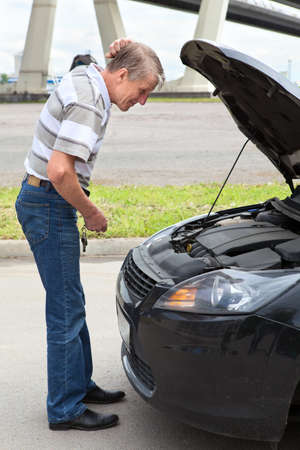 Confused mature driver standing in front of car with opened engine compartment hood photo
