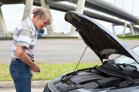 Confused mature driver standing in front of vehicle with opened engine compartment hood photo
