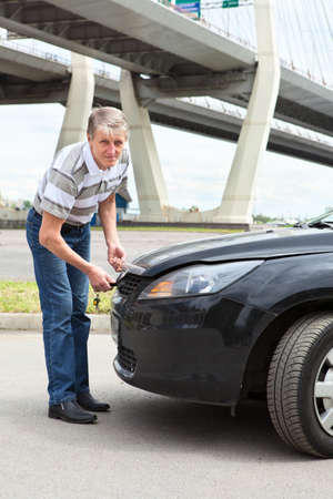 open autocar auto: Mature driver trying to open engine compartment hood standing in front of car