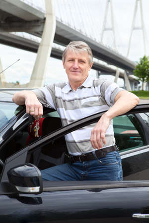 Happy mature driver with ignition key standing near the car Stock Photo - 14386019