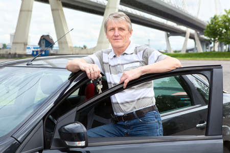 Happy mature driver with car key standing near the land vehicle photo