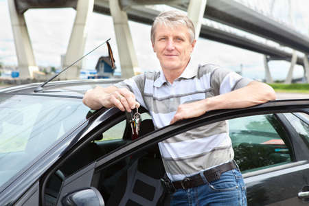 Happy mature driver with car key standing near own land vehicle Stock Photo - 14386022