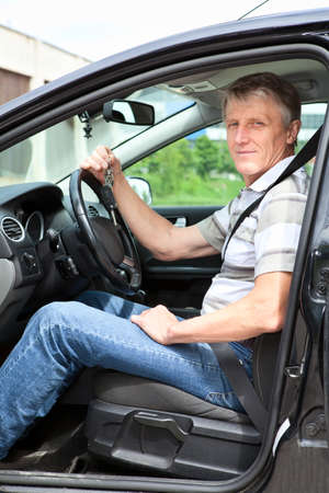 Happy mature man with car key sitting in own land vehicle photo