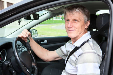 Happy mature driver with car key sitting in own car photo