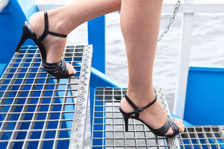 Piernas femeninas en medias de rejilla y zapatos de tacones altos pasando escaleras photo